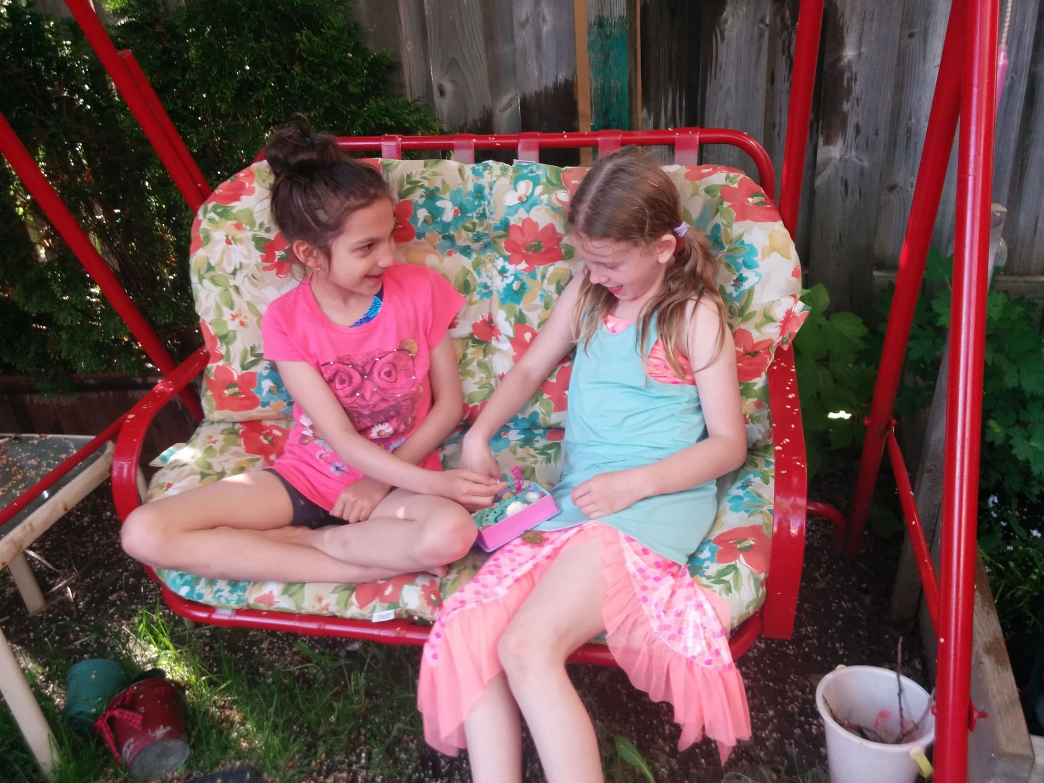 Two girls playing with Polly Pocket dolls on a red swing