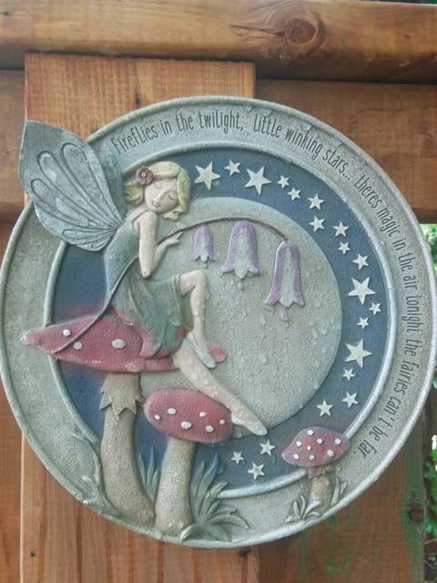 A garden plaque with a fairy surrounded by stars. The plaque reads: Fireflies in the twilight, little winking stars... There's magic in the air tonight, the fairies can't be far.""