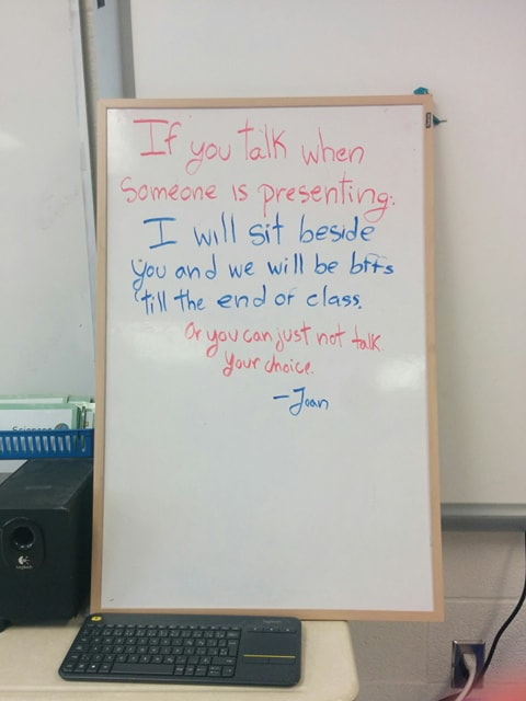"A whiteboard on which is written: ""If you talk when someone is presenting I will sit beside you and we will be BFFs till the end of class. Or you can just not talk, your choice. -Joan"""